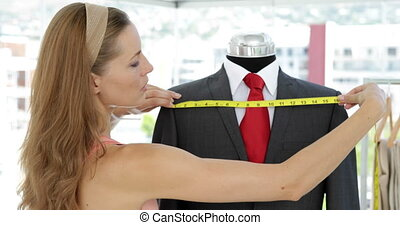 Pretty fashion designer measuring suit on mannequin in her...
