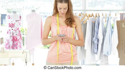 Attractive fashion designer texting
