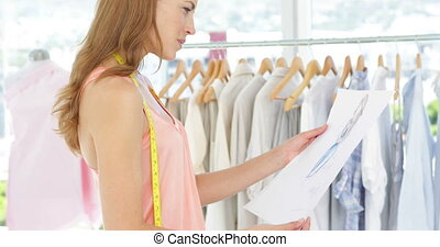 Attractive fashion designer looking at sketch in her studio