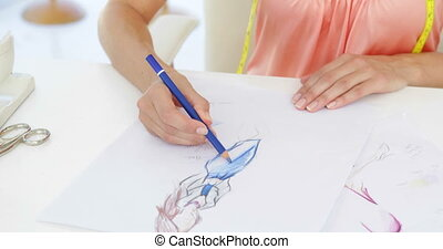 Attractive fashion designer sketching a dress design in her...
