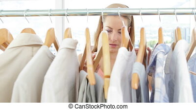 Attractive fashion designer looking at clothes on rail in...