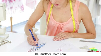 Attractive fashion designer sketching a design in her studio