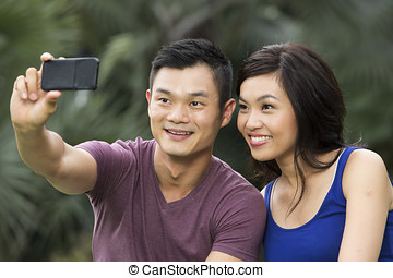 Chinese Couple taking photo of themselves with smartphone -...