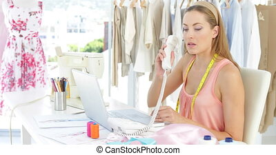 Attractive fashion designer working on laptop and answering...
