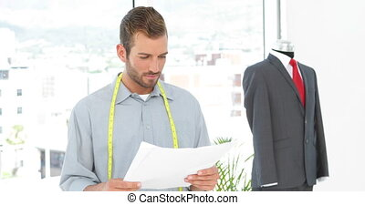 Handsome fashion designer looking at sketches and suit on...