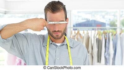 Handsome fashion designer holding a scissors smiling at...