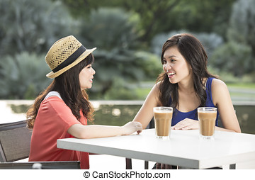 Two Young Women Enjoying Cup Of Coffee In Cafe