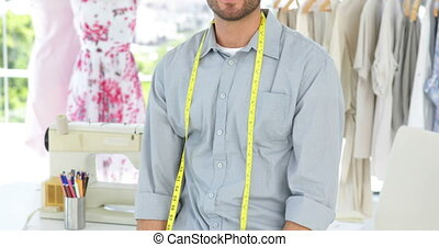 Handsome fashion designer smiling at camera with arms...