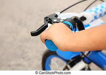 Handlebars and hand child in bicycle - Close up of...