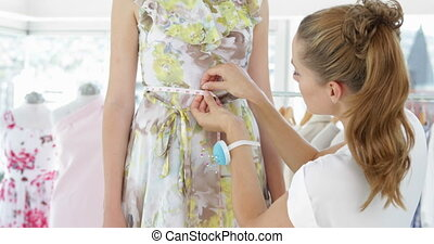 Pretty fashion designer measuring waist of dress on a model...