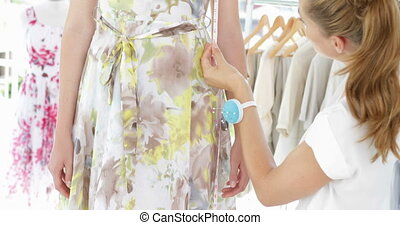 Pretty fashion designer measuring floral dress on a model in...
