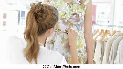 Pretty fashion designer tying belt of floral dress on a...