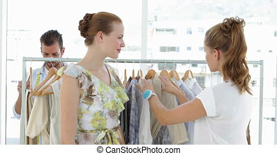 Fashion designer showing a dress to a model in her studio