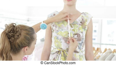 Pretty fashion designer measuring dress on a model in her...
