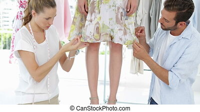 Fashion designers adjusting hemline of dress on a model in...