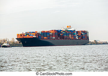 Fully laden container ship in port with its decks stacked...