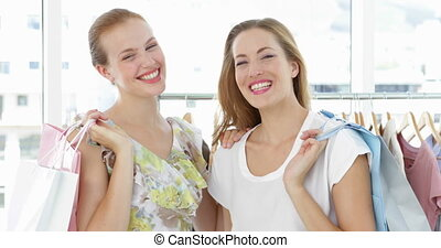 Two friends holding shopping bags smiling at camera in a...