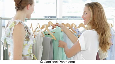 Two pretty friends looking through clothes rails at fashion...