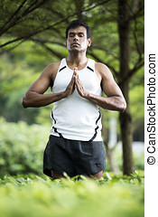 Indian man doing yoga exercise in park - Portrait of...