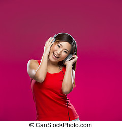 Happy Asian Woman listening to music on headphones. - Happy...