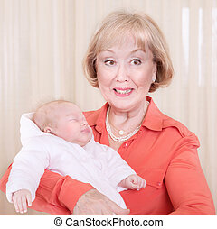 Grandmother with baby on hands at home, elegant young granny...