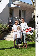 Happy Family holding Sold Sign - Young Happy Family holding...