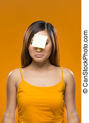 Forgetful Asian Woman with yellow sticky note on face -...