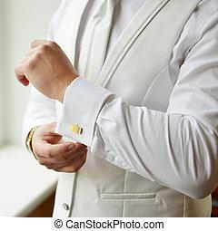 man's cufflinks - man puts cufflinks on sleeve white shirts
