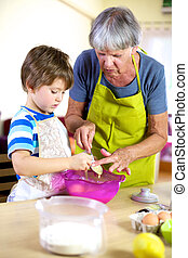 Senior woman helping grandson to cook and bake - Grandson...