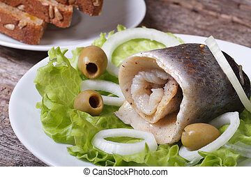herring roll with onion rings, olives and bread