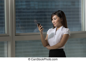 Young and pretty Chinese business woman standing using a...