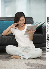 Asian woman at home reading a tablet PC. - Young Chinese...