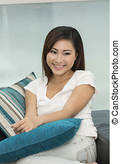 Young Asian woman at home on sofa relaxing.