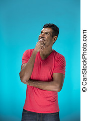 Excited Indian man looking up. Against blue background. -...