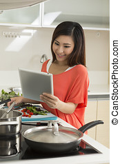 Asian woman in kitchen reading a recipe from a digital tablet. Young chinese woman in her twenties preparing food.