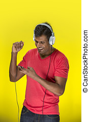 Happy Indian man wearing earphones singing and dancing to...