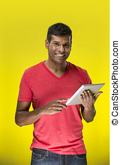 Indian man using a tablet PC In front of Yellow background....