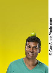 Happy Indian man balancing an Apple on his head