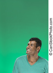 Excited Indian man looking up. Against green background. -...