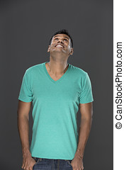 Excited Indian man looking up. Against grey background. -...