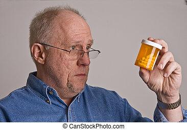 Older Man Looking at Prescription Bottle - An older bald man...