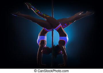 Slender pole dancers posing standing on hands - Image of...