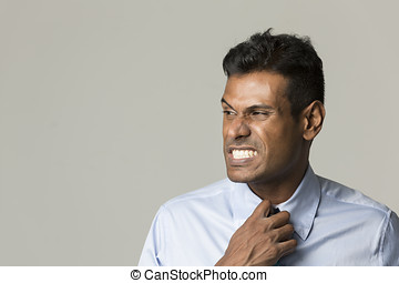 Indian business man adjusting his tie - Portrait of a angry...
