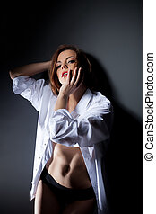 Sexy red-haired woman posing in white blouse
