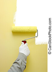 paint roller - Hand painting a white wall with a paint...