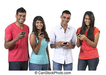 Group of young Indian friends using their smartphones. Happy...