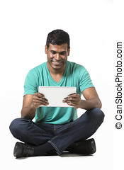 Happy Indian man using a tablet PC. Isolated on White...