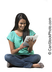 Young woman sitting on floor using a Digital Tablet PC...