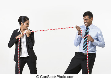 Two Indian business people playing tug war. Isolated on...