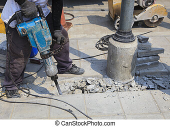 worker of road construction drilling cement ground use for...